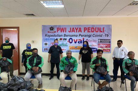 Abdul Mujid bersama teman ojol lainnya terima bantuan dari PWI Jaya Peduli. (Foto:Ist)