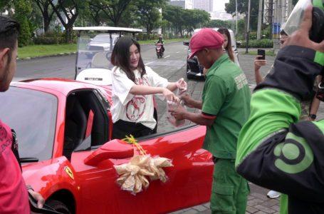 Aksi unik Shandy Purnamasari cantolkan kerupuk di Ferrari, sembari bagi sembako, di Surabaya. (Foto : Ist)